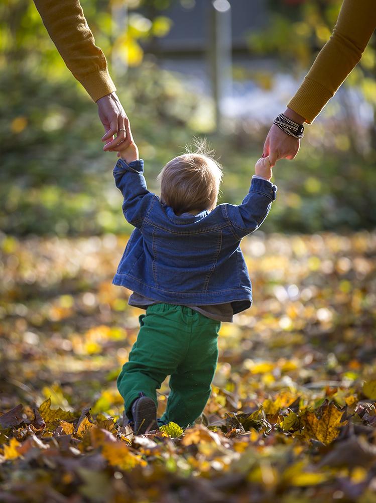 Kleinkind mit Eltern beim Spaziergang im Herbst