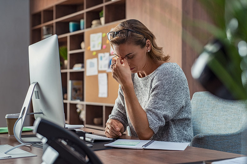 Exhausted businesswoman having a headache in modern office. Mature creative woman working at office desk with spectacles on head feeling tired. Stressed casual business woman feeling eye pain while overworking on desktop computer.